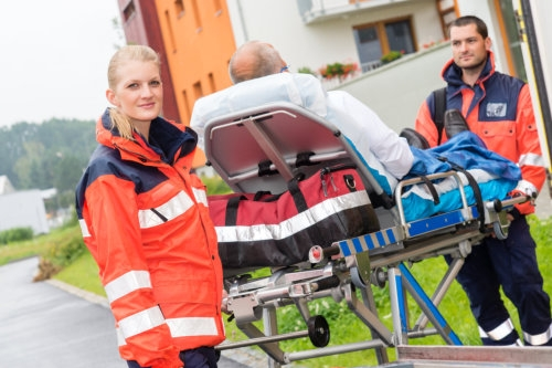 patient on stretcher with paramedics emergency aid